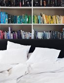 Bookcase organised by book colour against grey wall; untidy white bed linen on bed with black headboard in foreground