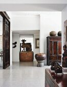 Indian sculpture of the bull Nandi on a rustic wooden trunk in the centre of a bright, spacious interior with antique Chinese furniture and objets d'art from around the world