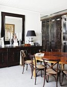 Elegant dining room with Chinese wooden partition and dark brown sideboard below large mirror; round, Chinese dining table in centre of room