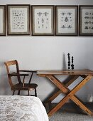 Framed drawings of insects on white wall above vintage table and chair