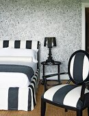 Black and white bedroom with intricately patterned wallpaper