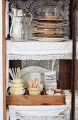 Offener Vitrinenschrank mit gestapelten Tellern neben Thermoskanne und Porzellangeschirr mit Besteck im Vintagestil mit Spitzendecken