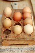 Hellbraune Eier in Vintage Eierbehälter aus Holz