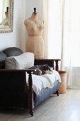 Hund auf gemütlichem Vintage Ledersofa neben alter Schneiderpuppe in Zimmerecke und Fenster mit geschlossenem Vorhang