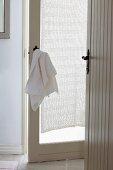Vorraum mit offenstehenden weißen Türen, Handtuch über nostalgischen Türdrücker gehängt