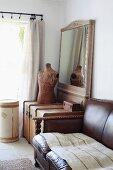 Traditionelles, braunes Ledersofa neben Holztruhe und Schneiderpuppe vor gerahmtem Spiegel in Zimmerecke neben dem Fenster