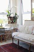 Rokoko Sitzbank mit naturfarbenem Bezug neben rundem Beistelltisch mit antikem Pflanzengefäss in Zimmerecke mit ländlichem Flair