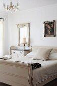Antikes Schlittenbett in hellem Farbton neben schlichtem Nachtkästchen und gerahmtem Spiegel an Wand