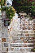 Blick von unten auf Naturstein Treppe und schmiedeeisernes Tor vor Terrassenplatz und Heckenwand in herrschaftlichem Ambiente