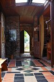 Red and black tiled floor in rustic, elegant foyer of country house