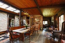 Dining area in rustic open-plan interior of simple country house