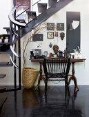 Wandtisch mit Fotorahmen und afrikanischen Dekogegenständen unter einer Innentreppe