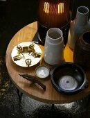 Holztisch mit Lampe, Keramikvasen und Schalen