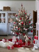 Decorated Christmas tree and presents on floor in rustic living room