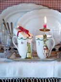 Mugs with Christmas decorations on silver tray in front of glasses and white porcelain dishes