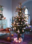 Decorated Christmas tree with presents on floor in interior of country house villa