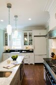 White country-house kitchen with island below traditional pendant lamps