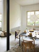 Zum Boden hin offener Raumteiler hinter Essplatz mit Klassiker Flechtstühlen und anthrazitfarbenem Metalltisch auf Flokatiteppich