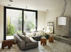 Überecksofa mit Hockertischen und Flokati vor Fensterschiebetür mit Blick auf begrünte Wand; moderne Kunst und Elefantenskulptur