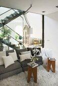 Graues Designersofa mit Zierkissen und Hockertische auf Flokati mit Glaswand als Trennung zur offenen Wohnraumtreppe