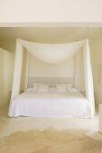 Puristischer Schlafplatz mit konvex drapiertem Stoffbaldachin und seitlichen Vorhängen in kahlem Raum