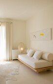 Moderne Malerei über einfacher Sofakonstruktion mit dicker Matratze und Polsterrolle in minimalistischem Wohnraum
