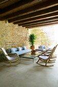 Mediterrane Wohnterrasse mit lässigen Polstersitzen, einer Reihe bequemer Schaukelstühle und modernen Stahlglas-Tischen
