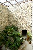 Grüne Pflanzen und ein Holzstuhl, umgeben von den hohen Natursteinmauern eines glasüberdachten Innenhofs