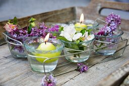Candle decoration with floating candles, lilac and fruit blossoms