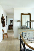 Landing and corridor in top storey of residential house with wrought iron staircase balustrade and vintage cabinet
