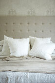 Pale scatter cushions on double bed in front of headboard upholstered in linen