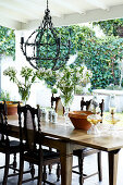 Stylish terrace, wrought iron lamp above a rustic, extension table with antique chairs