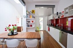 Bouquet of tulips on dining table in modern, open-plan kitchen with long kitchen counter and red glass splashback