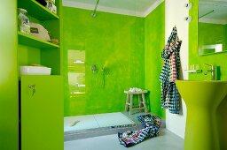 Designerbad mit grün marmorierten Wandflächen hinter Waschbecken und Duschbereich mit Glasabtrennung
