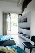 Gästezimmer mit weisser Einbauwand vor geöffneter Terrassentür