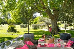 Set table and wicker armchairs on terrace with view into Mediterranean park