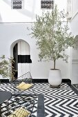 Tiled floor with black and white, graphic pattern in Moroccan courtyard