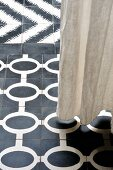 Floor-length linen curtain above different styles of black and white floor tiles with graphic patterns
