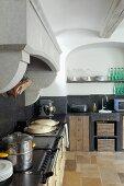 Vintage Küchenzeile mit Arbeitsplatte und Spritzschutz aus schwarzem Stein unter gemauertem Abzug in ländlicher Küche mit Rundbogen Wandnische