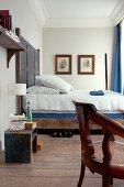 Rustikales Doppelbett mit Holz Kopfteil in Schlafzimmer mit Stuckfries an Decke
