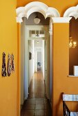 Ochre yellow walls with white-painted ornamentation and view into long corridor in period apartment