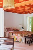 Ceiling structure painted orange above double bed with floral bed linen