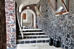 Stone porch area of Mediterranean house with steps leading under archway