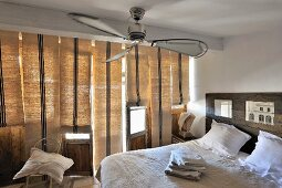 Modern bedroom with double bed below ceiling fan next to windows with closed Roman blinds