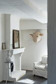 Armchair with loose cover in front of open fireplace and animal mask on wall in renovated, Mediterranean country house