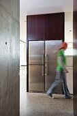 Open floor plan in a puristic home with exposed concrete walls - person running in front of a built in, stainless steel refrigerator