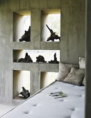 Day bad in front of an exposed concrete wall with a collection of old tree roots in the frameless window niches