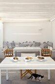 Gemauertes Sofa mit Kissen und Tische mit Regiestühlen auf überdachter Terrasse