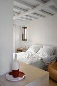 Doppelbett in einfachem Schlafzimmer; Teller und Flasche in rotweissem Keramikdesign