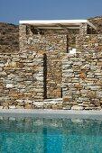 Natursteinmauern und türkis leuchtender Pool in griechischer Hügellandschaft
